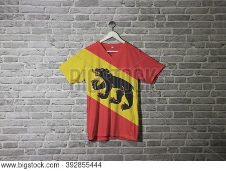 Bern Flag On Shirt And Hanging On The Wall With Brick Pattern Wallpaper. Coat Of Arms Of Berne The C