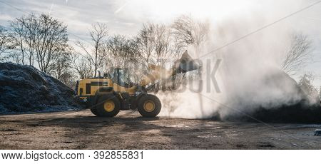 Wheel loader working on heap with biomass for composting on bright sunny day