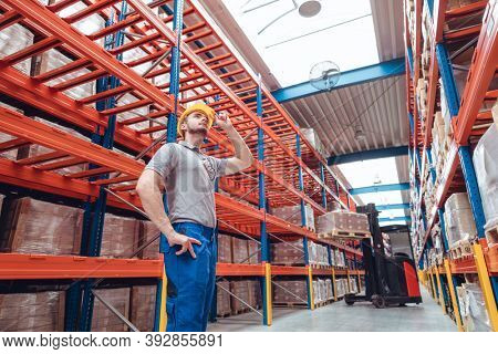Logistics worker standing in high bay warehouse in front of good waiting to be shipped