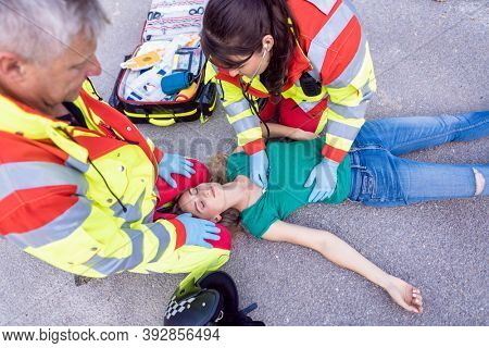 Paramedic and emergency doctor at site of traffic accident securing the victim