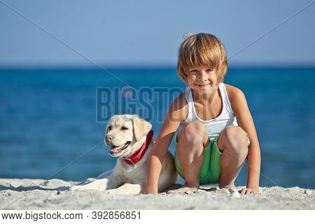 Happy Boy Playing With His Dog On The Seashore Against The Blue Sky. Best Friends Have Fun On Vacati