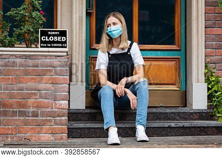 Caucasian Waitress Woman Wearing Medical Mask And Sorry Were Closed. Coronavirus Pandemic. Governmen