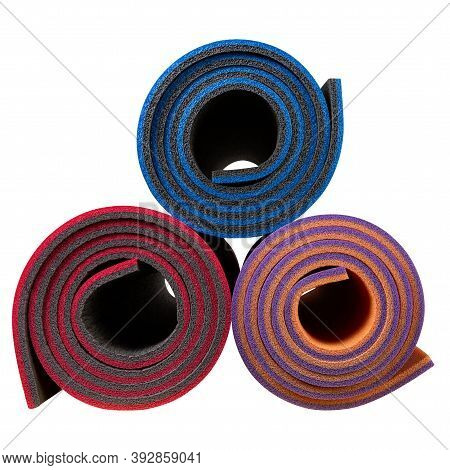 Three Colored Fitness And Yoga Mats, Twisted Into Rolls, End View, On White Background