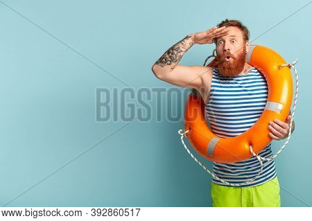 Vacation At Sea And Resort Concept. Stupefied Lifeguard With Lifebuoy Looks Surprisingly Into Distan