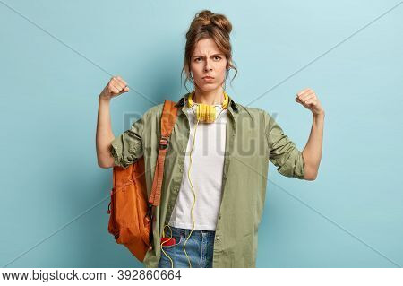 Powerful Strong Student Looks Angrily At Camera, Demonstrates Her Strength, Raises Hands, Shows Musc