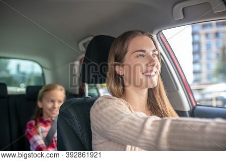 Smiling Mom Driving With Her Daughter Sitting On Backseat Of Car