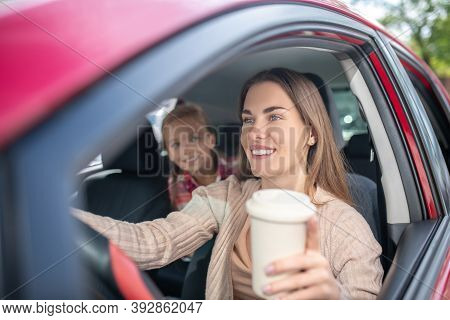 Smiling Mom Holding Coffee Cup, Driving With Her Daughter