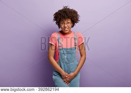 Unhappy Dark Skinned Woman Holds Crotch, Needs Toilet, Has Problematic Situation, Wears Pink T Shirt