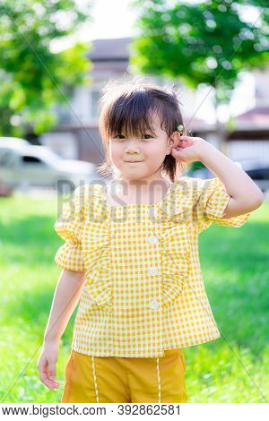Girl Pushed Her Ears With White Grass Flowers And Have Sweet Smile. Children Stand On The Green Lawn