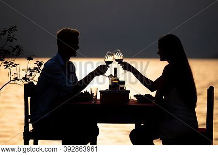 People, Vacation, Love And Romance Concept. Young Couple Enjoying A Romantic Dinner On Beach.