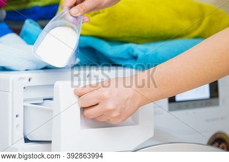 Washing Powder Detergent And Measuring Cup Pouring Into Machine. Household Duties, Clothes Laundry O