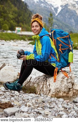 Tired Female Tourist Sits On Stones Near Little Stream In Mountains, Holds Professional Camera, View