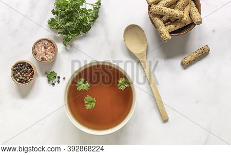 Flat Lay Of Homemade Beef Bone Broth In A Bowl With Ingredients. Contains Minerals And Healthy Nutri