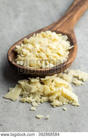 Grated white chocolate. Chocolate flakes in wooden spoon.