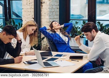 Businesswoman Boss Relaxing While Her Colleagues Working At Table In Office