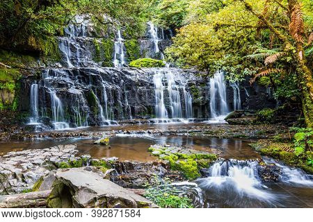 Travel to the ends of the world. New Zealand, South Island. Southern Scenic Route. Picturesque and magnificent waterfalls Purakaunui Falls. Picturesque multi-tiered cascading waterfalls.