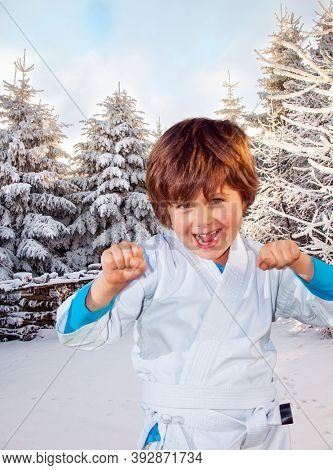 New Years is soon. Handsome boy in judo uniform training for judo. The northern winter sun is low above the horizon. Frosty snowy sunny day in winter coniferous forest