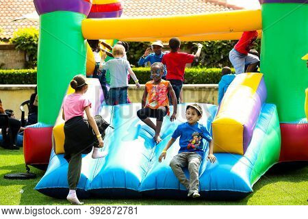 Diverse Children Having Fun On A Jumping Castle At Outdoor Funfair