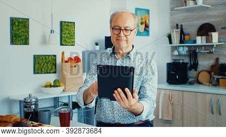Happy Older Man In Kitchen During Breakfat Using Tablet Pc. Elderly Person With Tablet Portable Pad