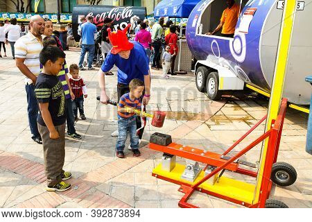 Child Minder Assisting A Boy To Hit A Strength Tester At Outdoor Funfair
