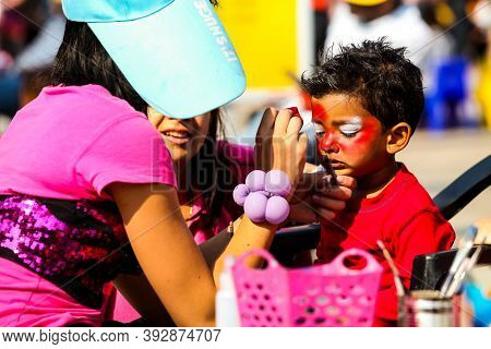Young Indian Child Getting A Spiderman Face Paint Mask At Festival