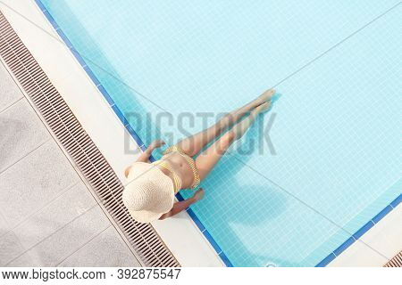 Woman relaxing in swimming pool on summer vacation. Hot sunny holiday concept. Top view flat lay