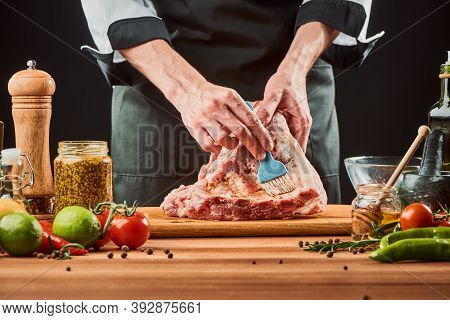 Chef Brushing Raw Beef Ribs With Marinade
