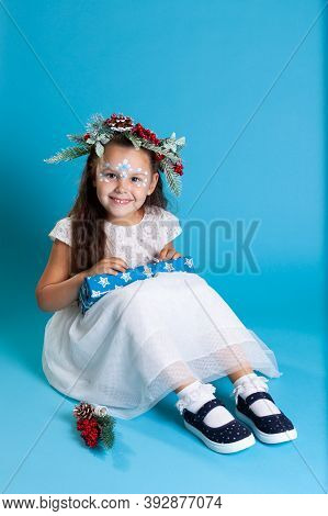 A Beautiful Girl In A White Dress, Wearing A Wreath And Sneakers Sits On The Floor And Unfolds A Box