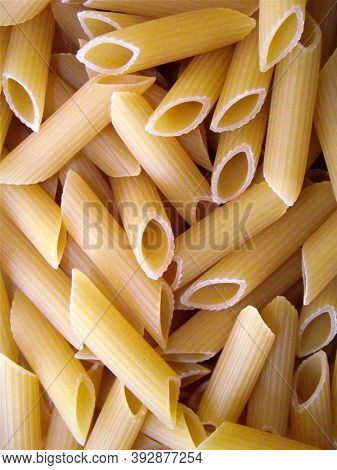 Raw Pasta. Penne Flat Lay. Pasta Secco Photo Texture. Dry Pasta Penne Scatter Top View. Whole Wheat