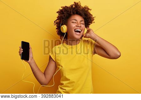 People, Music, Emotions Concept. Delighted Carefree Female With Afro Hairstyle Dances In Rhythm Of M