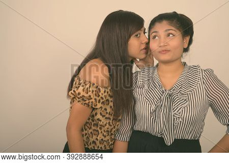 Studio Shot Of Young Persian Woman Whispering To Young Fat Persian Teenage Girl Thinking Against Gra