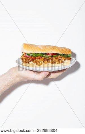 Hand Holding Vegan Banh Mi Sandwich With Roasted Cauliflower And Pickled Vegetables On White Plate.
