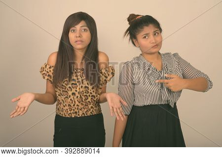 Studio Shot Of Young Fat Persian Teenage Girl Pointing At Young Persian Woman Looking Confused Again