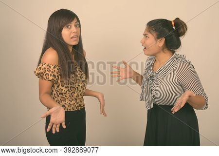 Studio Shot Of Young Fat Persian Teenage Girl Looking At Confused Young Persian Woman Against Gray B