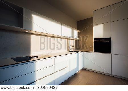 New Modern White Kitchen In Minimalist Design, During Morning Sunrise Hour, With Modern Appliances,