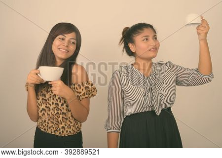 Young Happy Persian Woman Holding Coffee Cup With Young Fat Persian Teenage Girl Holding Empty Coffe