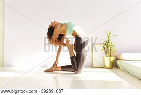 Side View Of Calm Female In Sportswear Practicing Yoga In Firefly Pose While Balancing On Arms On Ma