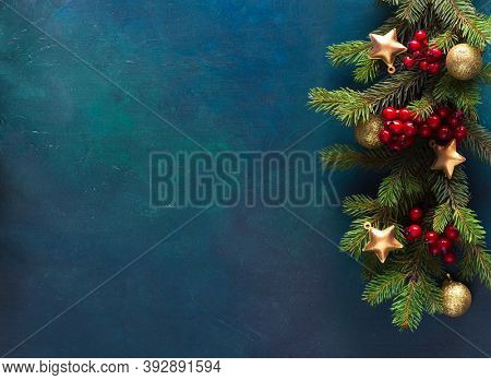 Fir branch with Christmas decoration on a  dark blue-green painted wooden background.  Flat lay.   New Year and Christmas  background with place for text.