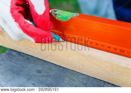 The Carpenters Hands In Work Gloves Draw A Line With A Pencil Along The Board Along The Ruler.