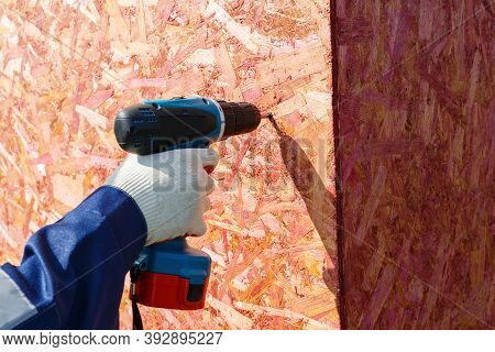 A Gloved Mans Hand Holds A Screwdriver And Fixes A Wooden Panel To The Wall.