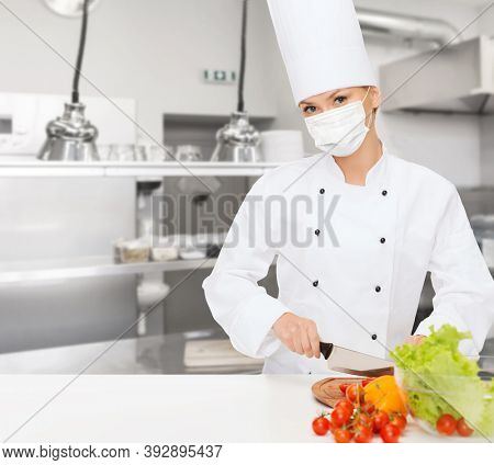 cooking, culinary and health concept - female chef in toque wearing face protective medical mask for protection from virus disease cutting vegetables over kitchen background