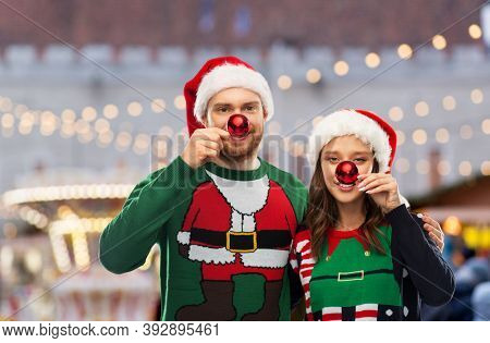 people and holidays concept - portrait of happy couple in santa hats and ugly sweaters making noses of red christmas balls over christmas market background