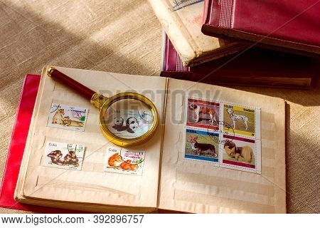 Lviv/ Ukraine - 10 26 2020: Old Vintage Collectible Postage Stamps Albums And Magnifying Glass, Phil
