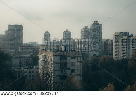 Cityscape With Tall Old Residential Houses In Haze Of Polluted Air. Between The Houses, Streets Are