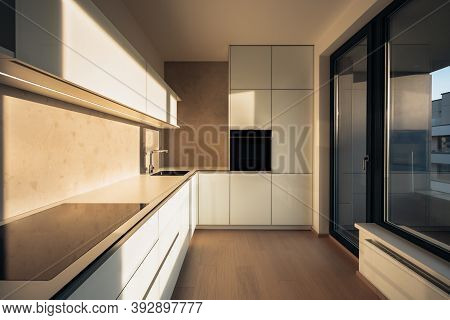 Minimalist Kitchen In City Apartment During Early Morning. There Are Modern Appliances And Premium M