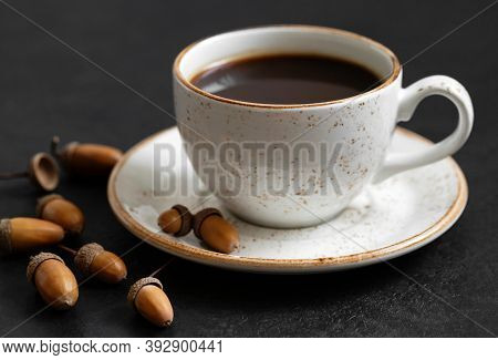Black Coffee In A White Cup And Acorns. Acorn Coffee On A Black Background. The Concept Of A Caffein