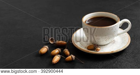 Acorn Coffee On A Black Background. A Cup Of Black Coffee And Acorns. Caffeine Substitute Concept. C