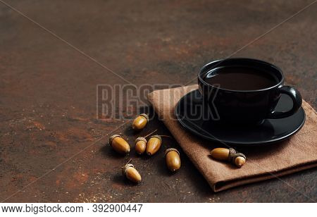 Coffee In A Black Cup And Acorns On A Brown Background. Acorn Coffee Without Caffeine. Space For Tex
