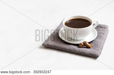 A Cup Of Black Coffee On A Gray Napkin. Acorn Coffee On A White Background. Autumn Minimal Concept.