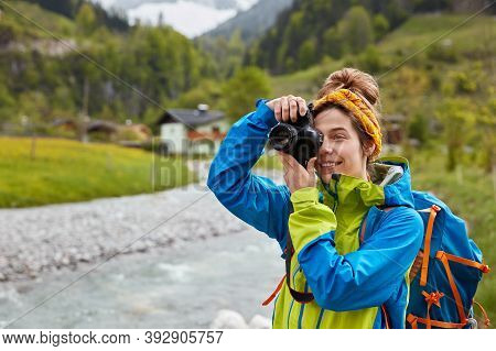 Pleased Young Female Traveler Makes Photo Of Mountain And River Landscape, Poses With Rucksack Again